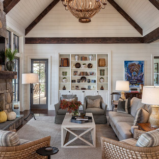 Large country open plan family and games room in Other with white walls, dark hardwood flooring, a standard fireplace, a stone fireplace surround, a wall mounted tv and brown floors.