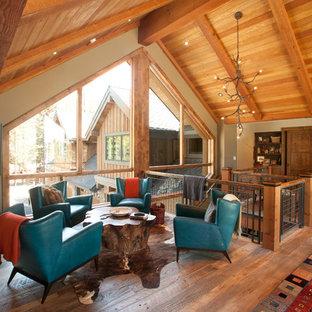 Idée de décoration pour une salle de séjour mansardée ou avec mezzanine design avec un mur beige et un sol en bois brun.