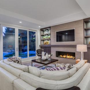 Cette photo montre une grande salle de séjour chic ouverte avec un mur gris, un sol en bois clair, une cheminée standard, un manteau de cheminée en carrelage et un téléviseur fixé au mur.
