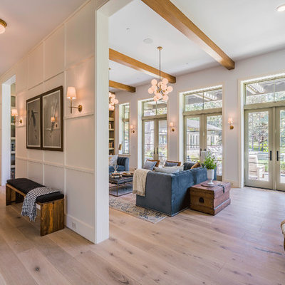 Huge trendy enclosed light wood floor and brown floor family room library photo in Los Angeles with white walls, no tv and no fireplace