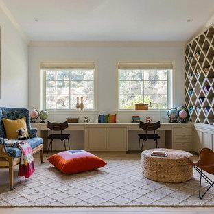 Cette photo montre une très grand salle de séjour avec une bibliothèque ou un coin lecture nature fermée avec un mur beige, un sol en bois clair, un sol beige et aucun téléviseur.
