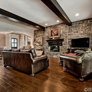リトルロックの中くらいのラスティックスタイルのおしゃれなオープンリビング (濃色無垢フローリング、標準型暖炉、石材の暖炉まわり、据え置き型テレビ、マルチカラーの壁、茶色い床) の写真