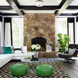 Modelo de sala de estar tradicional renovada con paredes blancas, chimenea tradicional, marco de chimenea de piedra, televisor colgado en la pared y suelo gris