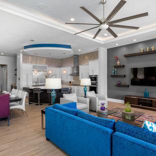 Foto di un grande soggiorno moderno aperto con pareti bianche, pavimento in gres porcellanato e TV a parete