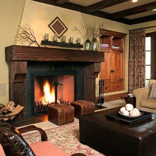 Modelo de sala de estar rústica con paredes beige, chimenea tradicional y marco de chimenea de madera