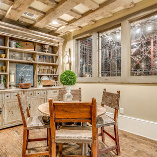 Esempio di un ampio soggiorno stile rurale aperto con pareti beige, pavimento in legno massello medio, camino classico, cornice del camino in cemento, angolo bar e porta TV ad angolo