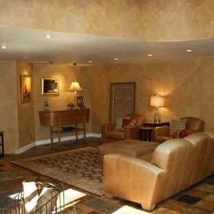 サンフランシスコの大きいトロピカルスタイルのおしゃれなファミリールーム (オレンジの壁、スレートの床、コーナー設置型暖炉、石材の暖炉まわり、コーナー型テレビ) の写真