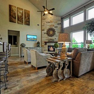 オースティンの大きいトラディショナルスタイルのおしゃれなファミリールーム (ベージュの壁、無垢フローリング、コーナー設置型暖炉、石材の暖炉まわり、壁掛け型テレビ) の写真