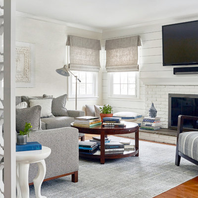 Inspiration for a mid-sized transitional enclosed medium tone wood floor and brown floor family room remodel in New York with white walls, a wall-mounted tv, a standard fireplace and a brick fireplace
