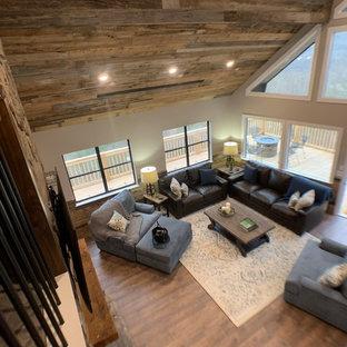 Idée de décoration pour une grande salle de séjour chalet ouverte avec un mur beige, sol en stratifié, un manteau de cheminée en pierre, un téléviseur fixé au mur et un sol gris.
