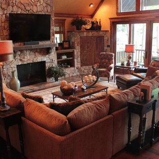 Cette image montre une grande salle de séjour craftsman ouverte avec un mur beige, un sol en bois foncé, une cheminée standard, un manteau de cheminée en pierre, un téléviseur fixé au mur et un sol beige.