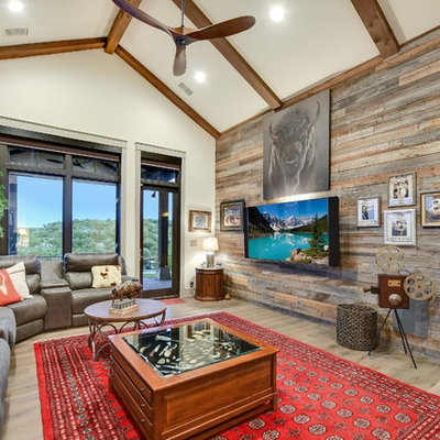 Example of a mountain style enclosed light wood floor and beige floor family room design in Austin with beige walls and a wall-mounted tv