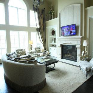 ヒューストンの大きいトラディショナルスタイルのおしゃれなファミリールーム (ベージュの壁、濃色無垢フローリング、標準型暖炉、コンクリートの暖炉まわり、壁掛け型テレビ、茶色い床) の写真