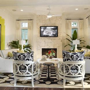 タンパの中サイズのトロピカルスタイルのおしゃれな独立型ファミリールーム (マルチカラーの壁、濃色無垢フローリング、標準型暖炉、石材の暖炉まわり、壁掛け型テレビ、茶色い床) の写真