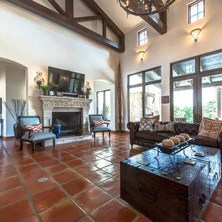 オースティンのサンタフェスタイルのおしゃれなファミリールーム (ベージュの壁、テラコッタタイルの床、標準型暖炉、石材の暖炉まわり) の写真