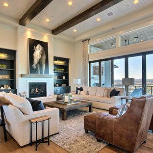 Пример оригинального дизайна: огромная открытая гостиная комната в стиле кантри с домашним баром, бежевыми стенами, светлым паркетным полом, стандартным камином и коричневым полом без ТВ