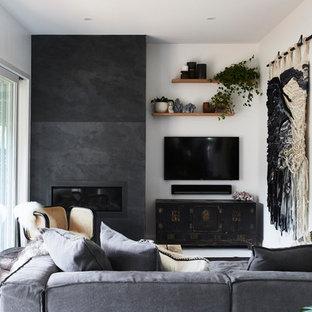 Immagine di un soggiorno tropicale di medie dimensioni e aperto con pareti bianche, pavimento in legno verniciato, camino classico, cornice del camino in pietra, pavimento bianco e TV a parete