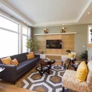 Immagine di un soggiorno scandinavo di medie dimensioni e aperto con pareti verdi, parquet chiaro, camino bifacciale, cornice del camino in pietra e TV a parete