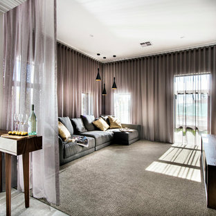 Foto de sala de estar contemporánea, sin chimenea, con paredes grises, moqueta y televisor colgado en la pared