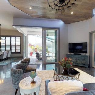 マイアミの巨大なビーチスタイルのおしゃれなファミリールーム (グレーの壁、コンクリートの床、暖炉なし、壁掛け型テレビ、黒い床) の写真