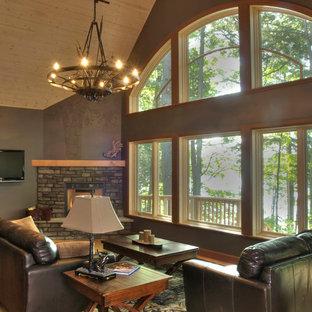 バンクーバーの広いラスティックスタイルのおしゃれなオープンリビング (茶色い壁、無垢フローリング、コーナー設置型暖炉、石材の暖炉まわり、壁掛け型テレビ) の写真