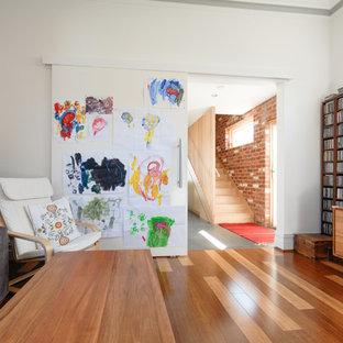 Inredning av ett industriellt mellanstort allrum med öppen planlösning, med ett musikrum, vita väggar, mellanmörkt trägolv, en fristående TV och flerfärgat golv