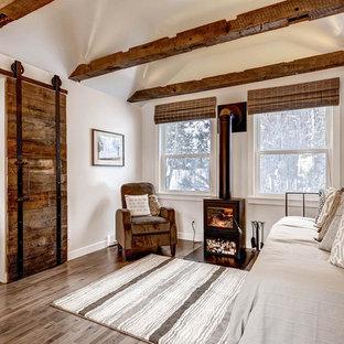 Cette photo montre une petit salle de séjour nature ouverte avec un mur gris, un sol en bois brun, un téléviseur fixé au mur et un poêle à bois.