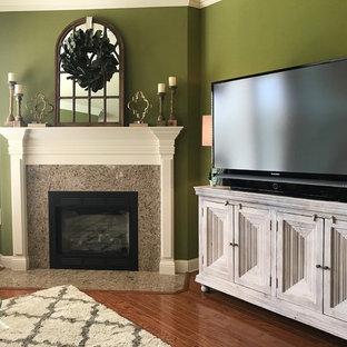 Inspiration pour une salle de séjour traditionnelle de taille moyenne et ouverte avec un mur vert, un sol en bois brun, une cheminée standard, un manteau de cheminée en carrelage, un téléviseur indépendant et un sol marron.
