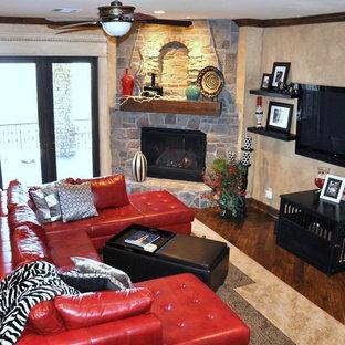 オクラホマシティの中サイズのトランジショナルスタイルのおしゃれなファミリールーム (ベージュの壁、無垢フローリング、コーナー設置型暖炉、石材の暖炉まわり、壁掛け型テレビ) の写真