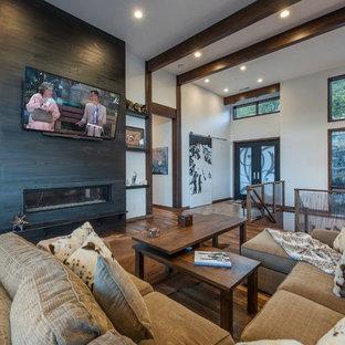Ejemplo de sala de estar abierta, actual, con paredes blancas, chimenea lineal, televisor colgado en la pared, suelo marrón, suelo de madera oscura y marco de chimenea de metal