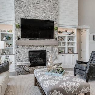 Immagine di un soggiorno american style di medie dimensioni e aperto con pareti beige, pavimento in legno massello medio, camino classico, cornice del camino in pietra e TV a parete