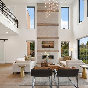 Ejemplo de sala de estar abierta, actual, grande, con paredes blancas, suelo de madera en tonos medios, chimenea tradicional, televisor colgado en la pared, marco de chimenea de piedra y suelo beige