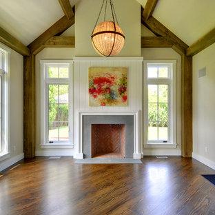 Réalisation d'une salle de séjour tradition de taille moyenne et fermée avec un mur beige, un sol en bois foncé, une cheminée standard, un manteau de cheminée en béton et aucun téléviseur.