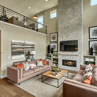 Photo of an arts and crafts open concept family room in Seattle with grey walls, light hardwood floors, a standard fireplace, a stone fireplace surround and a wall-mounted tv.