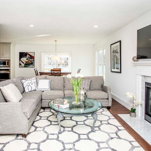 Mid-sized minimalist open concept medium tone wood floor and brown floor family room photo in Boston with gray walls, a standard fireplace, a stone fireplace and a wall-mounted tv
