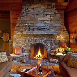 Inspiration for a large rustic open concept medium tone wood floor family room remodel in Vancouver with brown walls, a standard fireplace, a stone fireplace and no tv