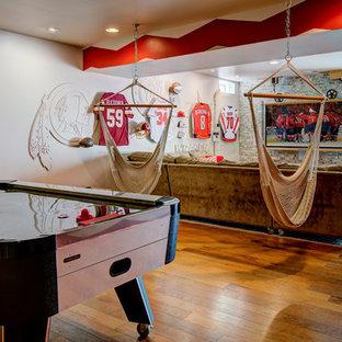 Diseño de sala de juegos en casa abierta, industrial, de tamaño medio, con paredes beige, suelo de madera en tonos medios y televisor colgado en la pared