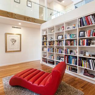 Exemple d'une salle de séjour avec une bibliothèque ou un coin lecture tendance avec un mur blanc et un sol en bois brun.