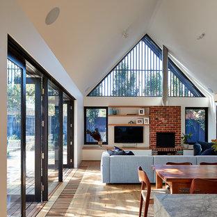 Diseño de sala de estar abierta, contemporánea, con paredes blancas, suelo de madera clara, televisor colgado en la pared, suelo marrón y chimenea tradicional