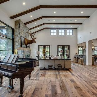Diseño de sala de estar con rincón musical abierta, campestre, extra grande, sin televisor, con paredes blancas, suelo de madera en tonos medios, estufa de leña, marco de chimenea de piedra y suelo multicolor