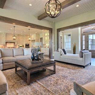Exemple d'une très grand salle de séjour craftsman ouverte avec un mur beige, un sol en bois foncé, une cheminée standard, un manteau de cheminée en pierre, un téléviseur fixé au mur et un sol marron.