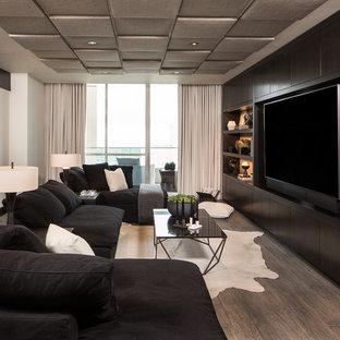 Imagen de sala de estar contemporánea, sin chimenea, con suelo de madera oscura, pared multimedia y suelo marrón