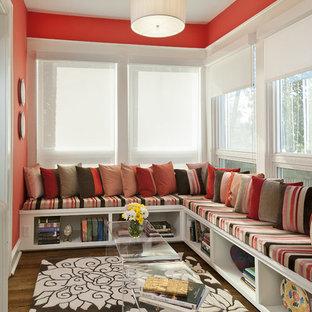 Immagine di un soggiorno design con libreria, pareti rosse e pavimento in legno massello medio