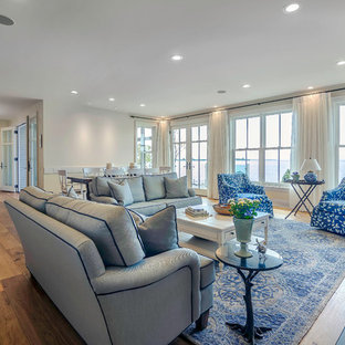 Example of a large coastal open concept medium tone wood floor family room design in Toronto with white walls, a standard fireplace, a brick fireplace and a media wall