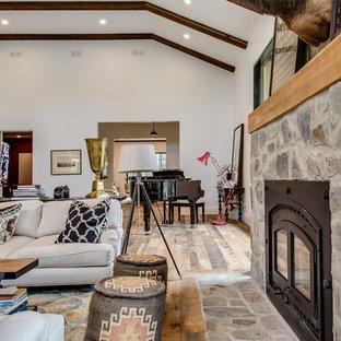 Foto de sala de estar con rincón musical abierta, campestre, extra grande, sin televisor, con paredes blancas, suelo de madera en tonos medios, estufa de leña, marco de chimenea de piedra y suelo multicolor
