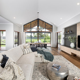 Photo of a large country open concept family room in Perth with a wall-mounted tv, white walls and light hardwood floors.