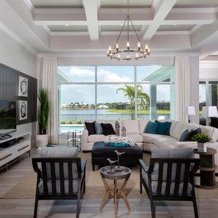Modelo de sala de estar abierta, costera, sin chimenea, con paredes blancas, televisor independiente y suelo beige
