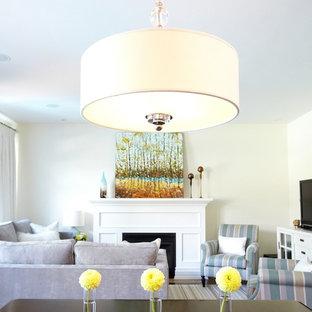 トロントの中サイズのトラディショナルスタイルのおしゃれな独立型ファミリールーム (白い壁、無垢フローリング、標準型暖炉、木材の暖炉まわり、コーナー型テレビ、茶色い床) の写真