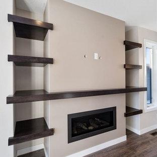 他の地域の大きいおしゃれなファミリールーム (ベージュの壁、ラミネートの床、横長型暖炉、壁掛け型テレビ、茶色い床) の写真
