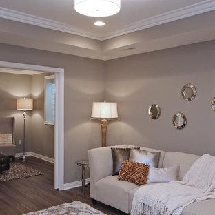 Modelo de sala de estar abierta, tradicional renovada, pequeña, con paredes grises y televisor colgado en la pared